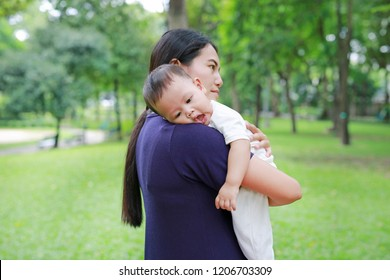 Asian mother carrying her infant baby boy in the summer garden.