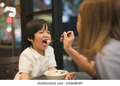 Asian Mother and child eating ice cream in cafe
