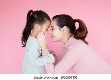 Asian mother and child girl playing, kissing and hugging