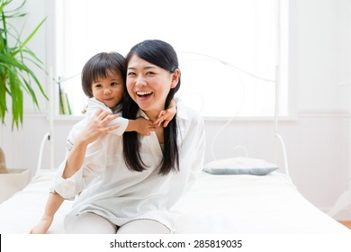 asian mother and child relaxing on the bed room