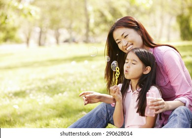 Asian mother and daughter blowing bubbles in park