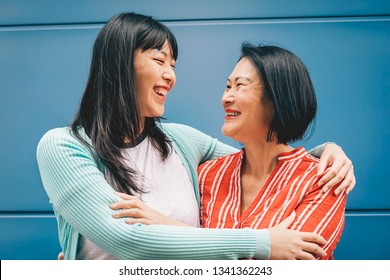 Asian mother and daughter embracing outdoor - Happy Chinese family enjoying time outside - Parenthood, love and people lifestyle concept
