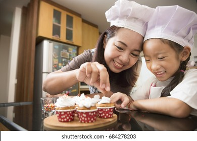 Asian mother and daughter enjoy making and decorate bakery cake in real life kitchen, Concept of family cooking