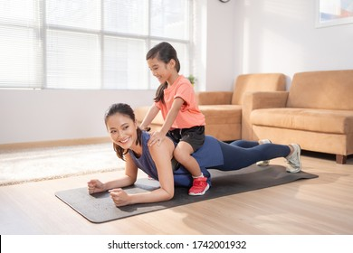 Asian mother and daughter Exercising at home they are having fun