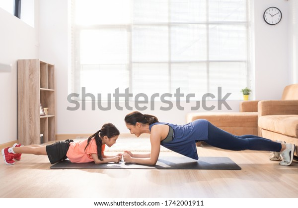 Asian mother and daughter exercising at home They are doing plank pose.