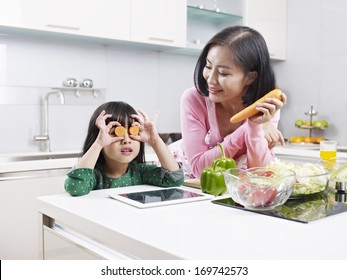 asian mother and daughter having fun in kitchen.