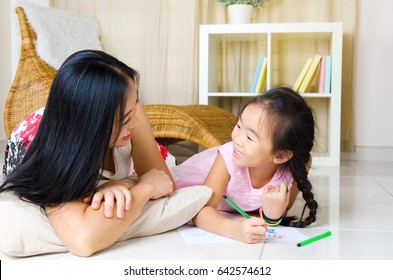 Asian mother and daughter lying on the floor and having conversation