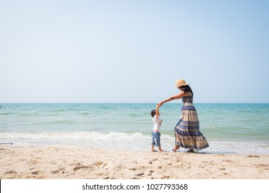 Asian mother and daughter are playing by dancing together on the beach with fully happiness moment, concept of love and relation in family lifestyle and learning by traveling for kid.