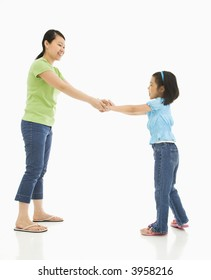 Asian mother and daughter playing together holding hands.