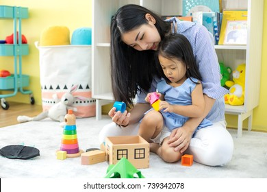 Asian mother and daughter playing toy in house