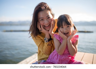 Asian mother daughter pose smile faces together, family relation