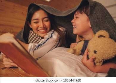 Asiatische Mutter und Tochter lasen nachts im Schlafzimmer ein Schlafgeschichten-Buch.