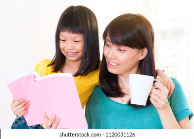 Asian mother and daughter read together