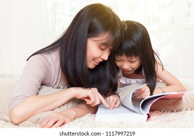 Asian mother and daughter reading a book together