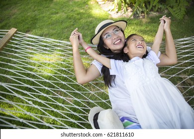 Asian mother daughter relaxing in hammock in the park , happy family spending time at beach and hammock
