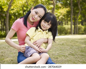 asian mother and daughter sitting on grass in a park.