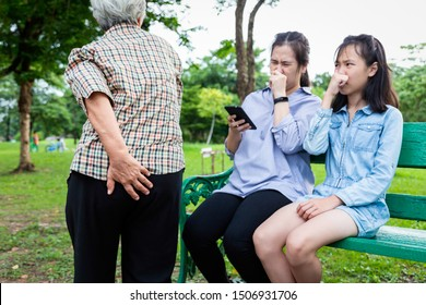 Asian mother and daughter squeezing nose with fingers,something stinky,senior grandmother holding her bottom,elderly people farting make a bad smell suffer from flatulence and gas in digestive tract
