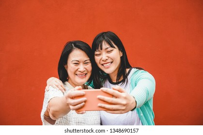 Asian mother and daughter taking selfie with smartphone for story app - Happy family people having fun with technology trends - Love, parenthood lifestyle, tech and tender moments concept