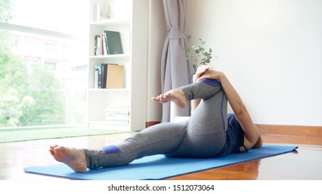 Asian mother and daughter teaching and practicing light yoga exercise on a mat, stretching and controlling the movements on various parts of the body in the brightly lit sunny morning living room