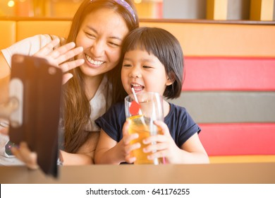 Asian Mother and daughter using smartphone video call camera in restaurant.Mother and daughter talking to each other through a video call on a smartphone.