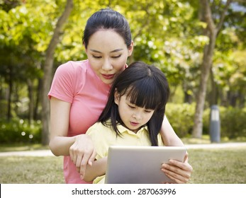asian mother and daughter using tablet computer outdoors.