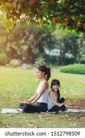 Asian Mother and daughter in white shirt and black trousers doing yoga exercises on grass in the park at the day time.sport and exercises for healthy lifestyle.