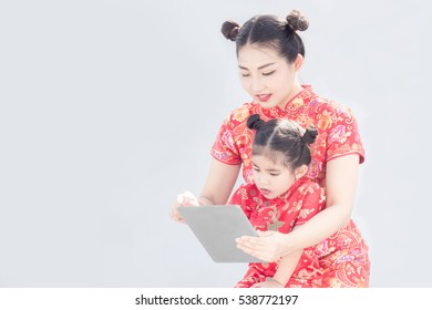 asian mother and duagther use tablet together for find something to gift in online shopping website