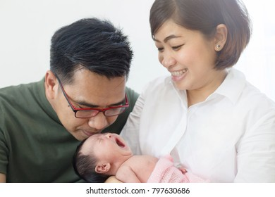 Asian Mother and Father take care their adorable newborn baby carefully