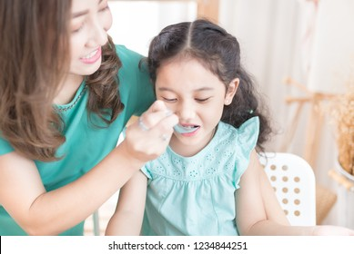 Asian mother feeding medicine to mouth of daughter, Asian children don't want to eat medicine, asian children eat food with metal spoon, child nutrition and development, family time, anorexia