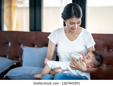 Asian mother feeding milk to her baby by bottle, this photo can use for family, mom, love, insurance concept