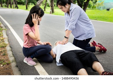 Asian mother first aid emergency CPR on unconscious senior grandmother while daughter calling ambulance,woman care,try to resuscitation patient,elderly with cardiac arrest,heart attack while exercise