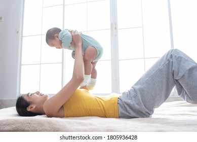 Asian mother fit and play Yoga for lose weight after delivery a new born baby in home, exercise and healthy concept.