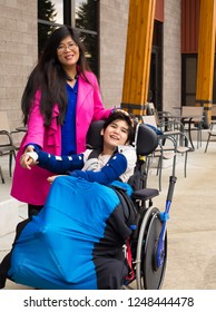 Asian mother in forties with eleven year old biracial disabled son in wheelchair outdoors