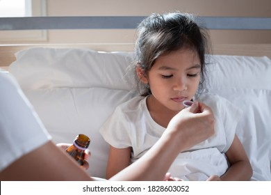 Asian mother giving cough syrup medicine on a spoon to her daughter in bed, Sick child and health care concept.