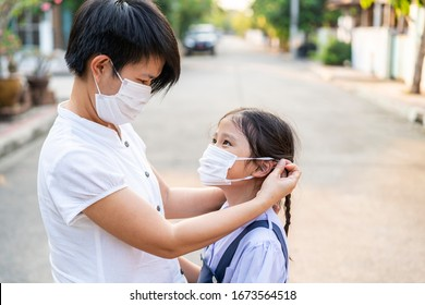 Asian mother help her daughter wearing medical mask for protection covid 19 virus outbreak situation. Covid 19, Corona, Virus outbreak, healthcare and medical, Social Distance or Asian family concept