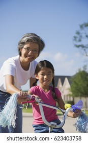 Asian mother helping daughter ride bicycle