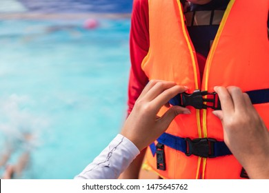 Asian mother helping her son to wear life jacket before playing in swimming pool, Selective focus.