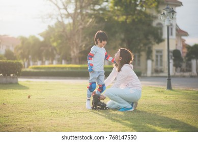 Asian mother helping her son putting his roller skates on enjoying time together in the park
