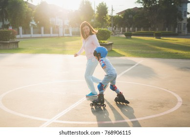 Asian mother helping her son to playing roller skate in the park