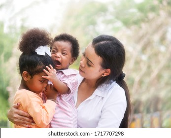 Asian mother and her children playing together in the park. A little boy crying while his sister tries to talk with him and wants him to stop crying.