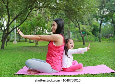 Asian mother and her daughter doing yoga in the public park.