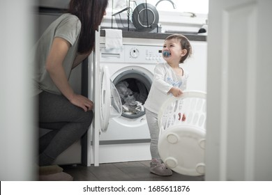 An Asian mother and her daughter enjoy and laugh doing the laundry in the kitchen of a house in Edinburgh, Scotland, United Kingdom, where a washing machine can be seen on the background