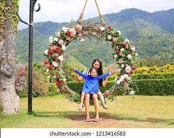 Asian mother and her daughter sitting on beautiful basket swing with the colorful roses flower in the nature garden hanging on pole under tree.