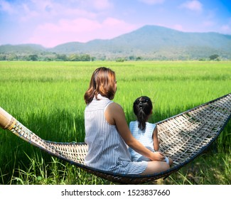 Asian Mother and her Daughter are  sitting in a hammock and looking at rice field and mountains .