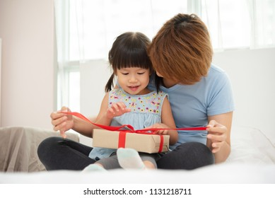 Asian mother and her daughter unwrapping gift box.  Mum and girl smiling and hugging on bed in their bedroom togetherness.