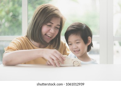 Asian mother and her son playing wooden car toy together