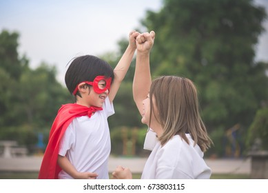 Asian Mother and her son playing together in the park,Boy in Superhero's costume.