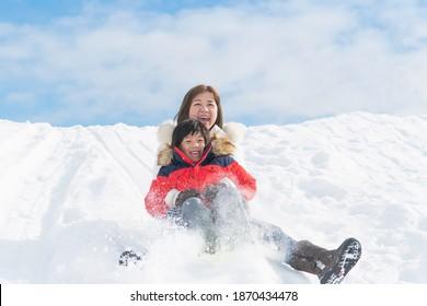 Asiatische Mutter und ihr Sohn rutschen im Winter auf Schlittelpiste