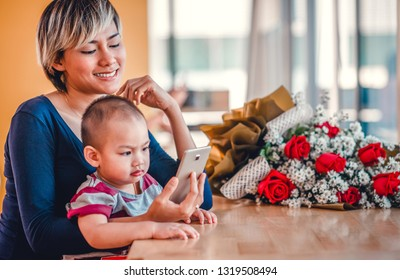 Asian mother and her son Viewing mobile phones Happy mood. Focus on the mother's face.