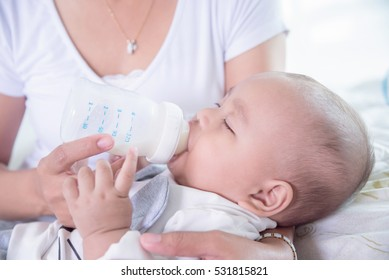 Asian mother holding and feeding milk for her child from plastic bottle at home